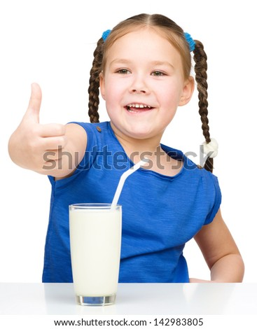 Cute little girl drinks milk using a drinking straw while showing thumb up sign, isolated over white - stock photo