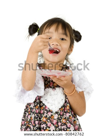 cute little girl eating a dessert, isolated on white background - stock photo