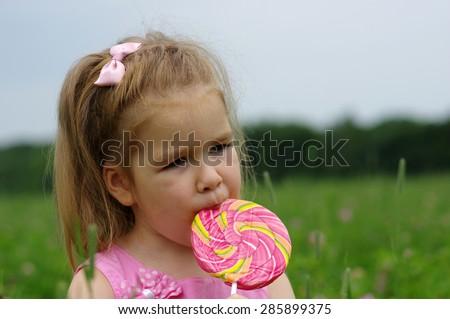 cute little girl eating a lollipop on the field  - stock photo