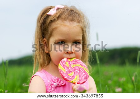 cute little girl eating a lollipop on the field  - stock photo