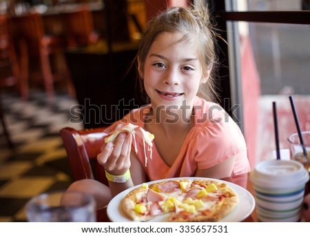 Cute little girl eating a piece of pizza in a restaurant - stock photo