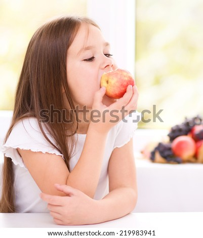 Cute little girl eating an apple - stock photo