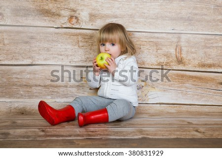 Cute little girl eating apple. studio shoot