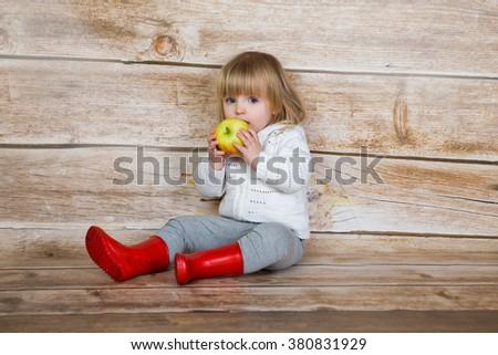 Cute little girl eating apple. studio shoot - stock photo