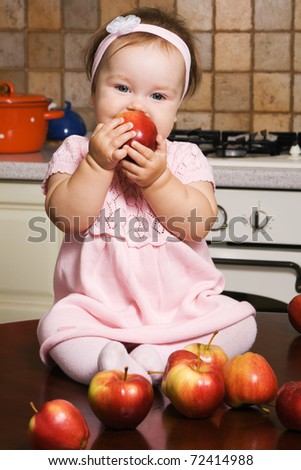 Cute little girl eating apples on kitchen - stock photo