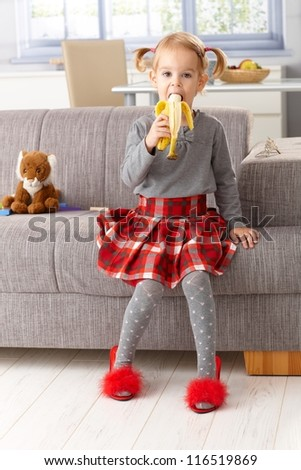 Cute little girl eating banana, wearing mother's high heel red slippers.