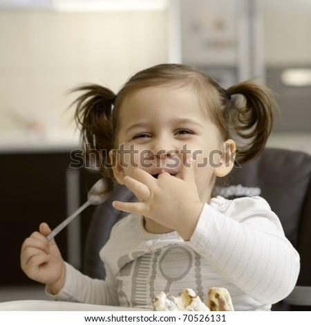 cute little girl eating cake - stock photo