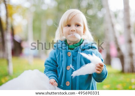 Cute little girl eating candy-floss outdoors at autumn
