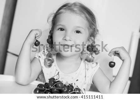 cute little girl eating cherries on white background  ( black and white ) - stock photo