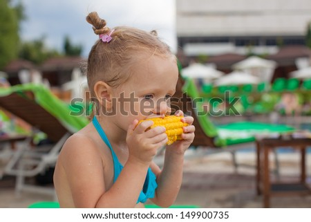 Cute little girl eating corn at the pool on vacation - stock photo