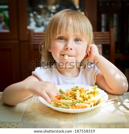 Cute little girl eating Fusilli - stock photo