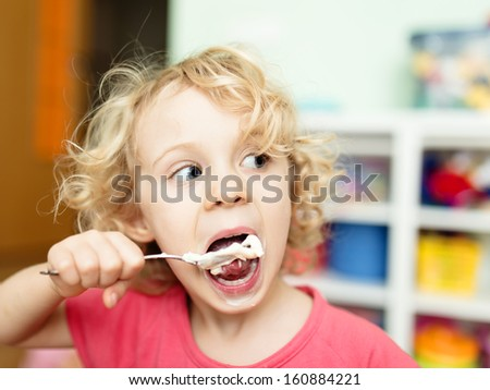 Cute little girl eating ice-cream - stock photo
