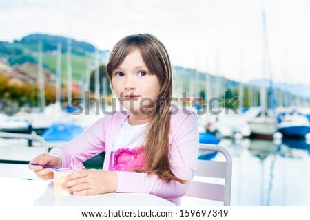 Cute little girl eating ice cream, outdoor portrait - stock photo