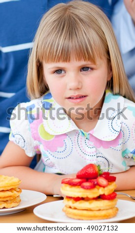 Cute little girl eating waffles with strawberries in the kitchen