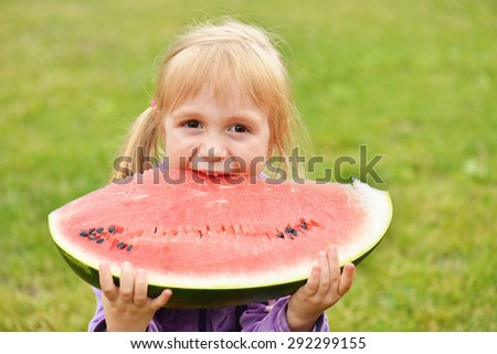 cute little girl eating watermelon on the grass - stock photo