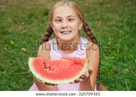 Cute little girl eating watermelon on the grass in summer time. with ponytail long hair and toothy smile sitting on grass and enjoying. funny with crossed eyes. - stock photo