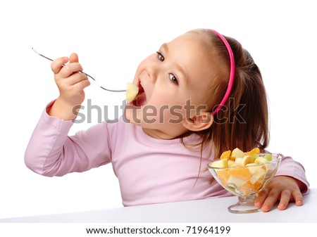 Cute little girl eats fruit salad using fork, isolated over white - stock photo