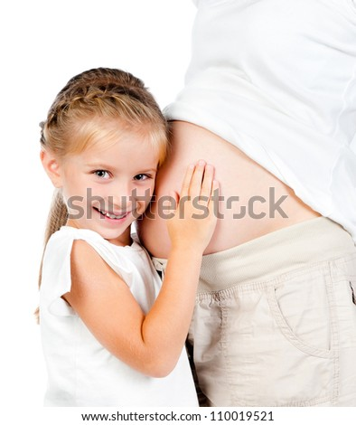 cute little girl embraces a stomach of pregnant mother - stock photo