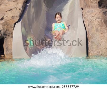 Cute little girl enjoying a wet ride down a water slide - stock photo