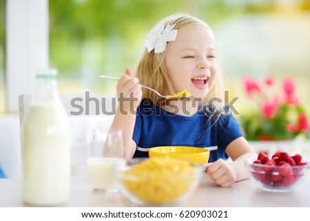 cute little girl enjoying her breakfast at home pretty child eating corn flakes and raspberries - Pictures Of Small Children