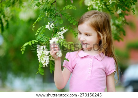 Cute little girl enjoying herself on hot and sunny summer day - stock photo