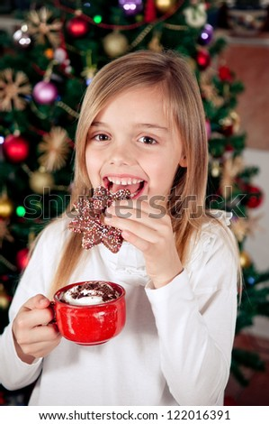 Cute little girl enjoying in christmas cookie and hot chocolate - stock photo