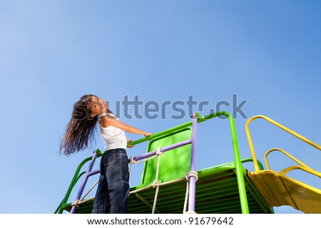 Cute little girl enjoys playing in a children playground - stock photo