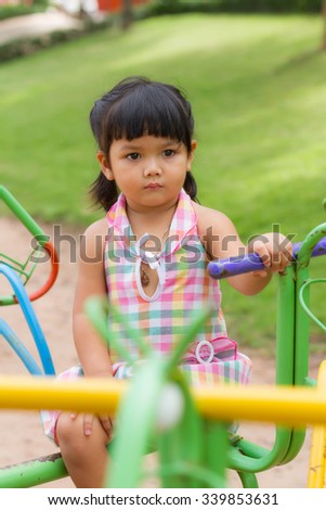 Cute little girl enjoys playing in a children's playground
