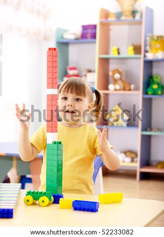 Cute little girl excited with tall column she built using building bricks in preschool - stock photo