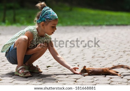 Cute little girl feeding squirrel at park - stock photo