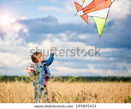 cute little girl flies a kite in a field of wheat - stock photo