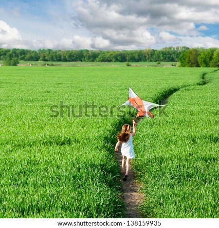 cute little girl flies a kite on grass in summer day - stock photo