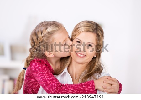 Cute Little Girl giving a kiss to her mother at home