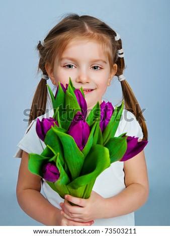 Cute little girl giving tulips. Studio shot - stock photo