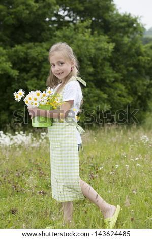 cute little girl harvesting flowers in a bucket - stock photo