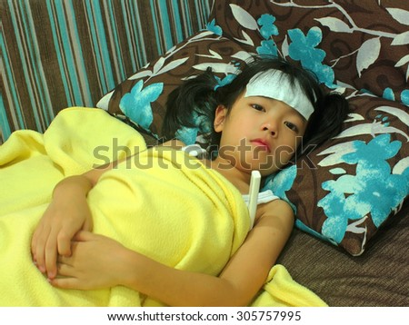 Cute little girl have a fever with a thermometer  - stock photo