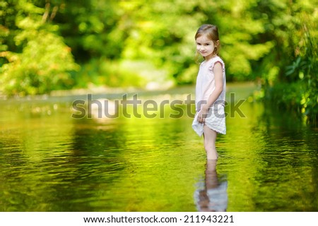 Cute little girl having fun by a river on warm and sunny summer day