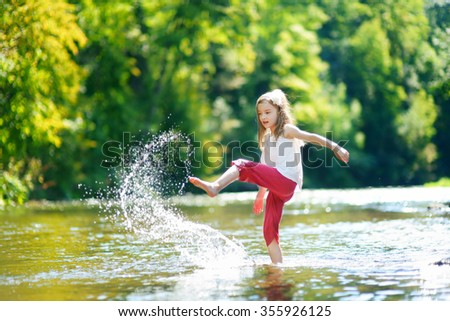 Cute little girl having fun by a river on warm and sunny summer day - stock photo