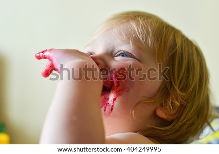 Cute little girl having fun eating. Girl with blonde hair having fun after spilling a cup of smoothie and smearing her face. Weekend, warm and cozy scene in the kitchen. - stock photo