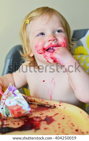 Cute little girl having fun eating. Girl with blonde hair having fun after spilling a cup of smoothie on the table. Weekend, warm and cozy scene in the kitchen. - stock photo