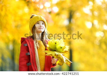 Cute little girl having fun on beautiful autumn day outdoors - stock photo