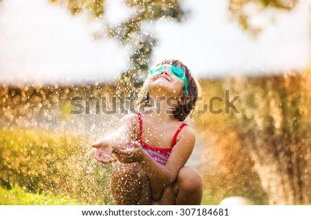 Cute little girl having fun outside in summer garden     - stock photo