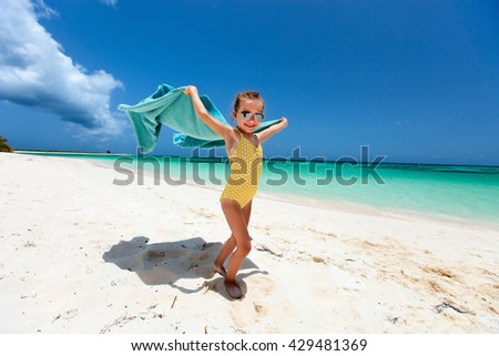 Cute little girl having fun running with towel and enjoying vacation on tropical beach with white sand and turquoise ocean water
