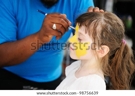 Cute little girl having her face painted on a hot summer day