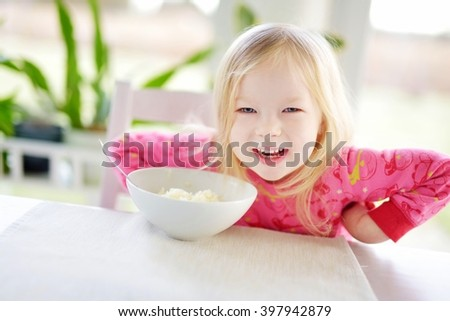 Cute little girl having oatmeal for breakfast at sunny kitchen