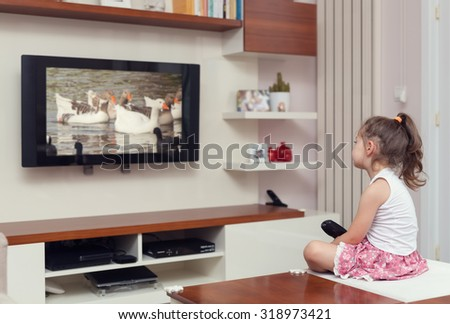 cute little girl having remote control and watching tv - stock photo
