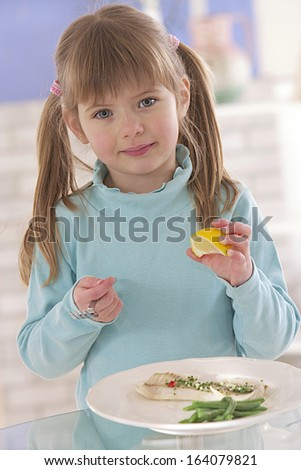 cute little girl healthy eating fish,vegetable dish with lemon - stock photo