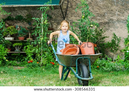 Cute little girl helping her mother in the backyard with heavy wheelbarrow - stock photo
