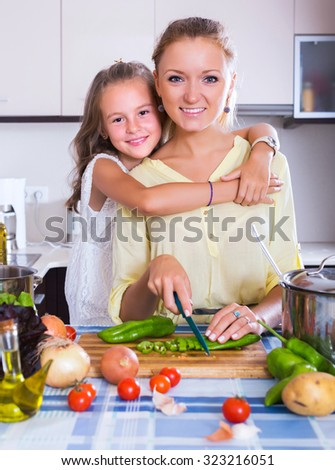 Cute little girl helping mother to prepare vegetables in kitchen at home