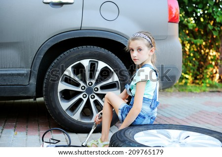 Cute little girl helps her father to change wheel on their family car on warm day in the yard  - stock photo